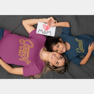Pregnant mom and daughter duo lying down wearing raising smart girls and smart like mama t-shirt