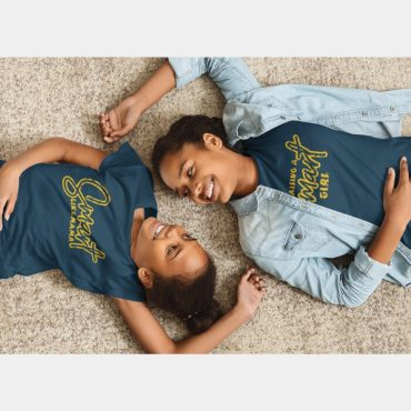 Mother and daughter duo lying down wearing raising a smart girl and smart like mama matching t-shirt
